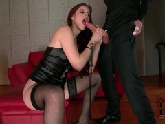 Redhead wears leather and stockings as she sucks movies at lingerie-mania.com