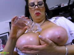 Mature secretary oils up her huge tits in the office clip