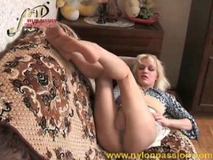 She rubs pantyhose feet on each other tubes