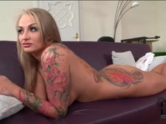 Tattooed blonde girl lies naked on the couch videos