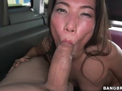 Asian brunette sucks off his cock in the car tubes at asian.sgirls.net