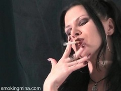 Beauty in big earrings and lipstick smokes cigarette videos