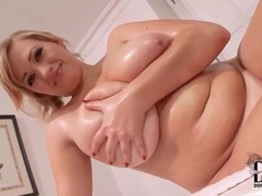 Curvy solo blonde rubs oil into her big tits tubes