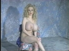 Solo blonde has gigantic fake tits to show off videos