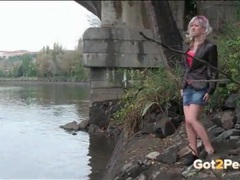 Blonde girl climbs down to the river to piss clip