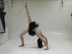 Ballerina in a black dress does standing splits tubes