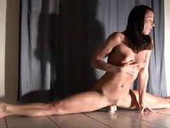 Flexible brunette does split and rides toy videos