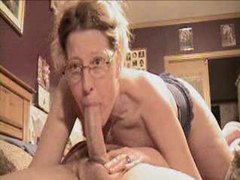 Woman in glasses deepthroats long cock clip