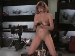 The fucking machine is poking her pussy while she rubs her clit tubes