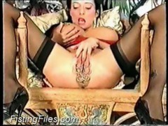 Girl with many vaginal piercings fisting her own hole tubes