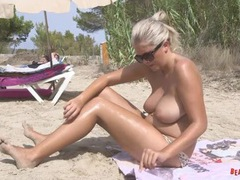 Big breasted beach babe oils up erotically tubes