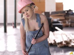 Young blonde sweeping a warehouse in her overalls tubes