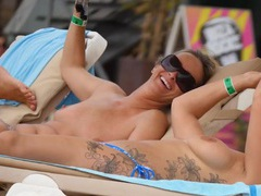 Tattooed girl and her topless friend tanning topless videos