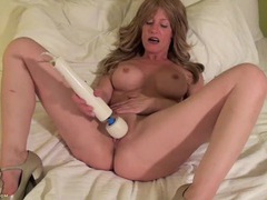 Milf in a hotel bed getting off with her magic wand movies at lingerie-mania.com