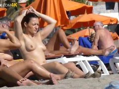 Pierced nipple babe oiling up on a public beach movies at adipics.com