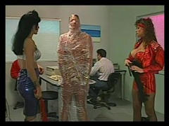 Mistresses cover a man in tight plastic wrap tubes