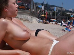 Voyeur lovingly films her natural tits at the beach videos