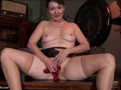 Chatty mom sits on a desk and plays with her pussy videos