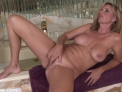 Milf sits by the bathtub and fingers her box videos