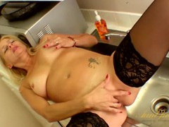 Mommy sits on the kitchen sink and fingers her twat videos