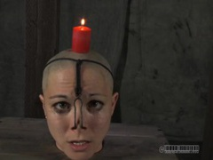Candle drips wax on the head of a bound girl videos