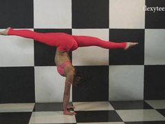 Athletic young lady in pink leggings is wonderfully flexible tubes