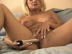 Shiny dildo slides into her mature pussy with ease clip