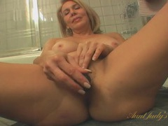 Naked mature chick toys her tight pussy in the bathroom movies at lingerie-mania.com